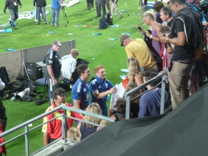 Steven Finn and Jonny Bairstow posing for photos and signing autographs for fans